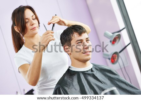 Female hairdresser at work making haircut