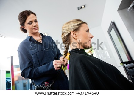 Female Hairdresser Braiding Client's Hair