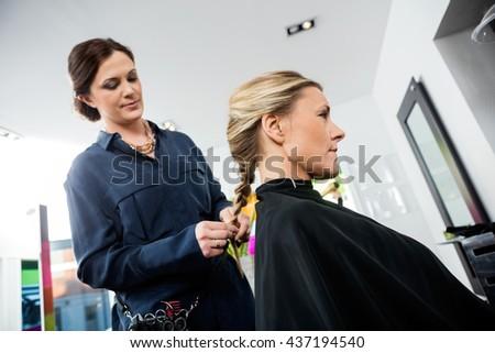 Female Hairdresser Braiding Client's Hair - stock photo