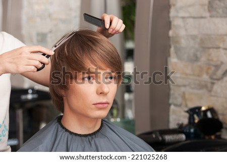 Female hairdresser cutting hair of man client. handsome man sitting in hair salon