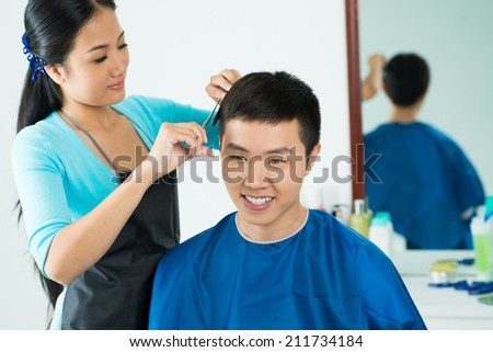 Female hairdresser cutting hair of smiling male client at beauty salon