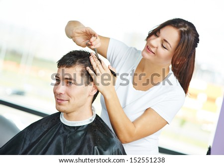 Female hairdresser cutting hair of smiling man client - stock photo