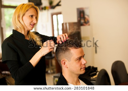 Female hairdresser cutting hair of smiling man client at beauty salon