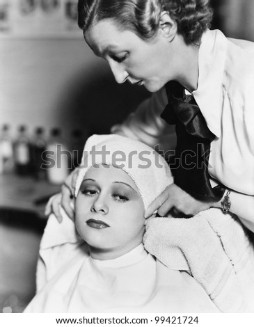 Female hairdresser drying hair of a young woman with a towel in a hair salon - stock photo