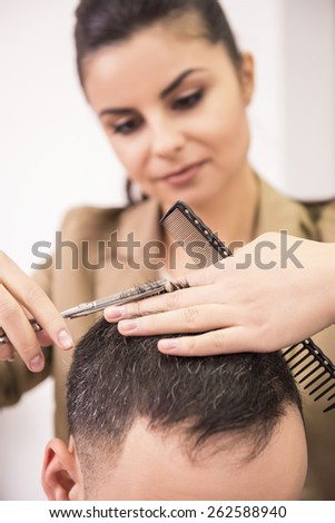 Female hairdresser is cutting hair of man client. - stock photo