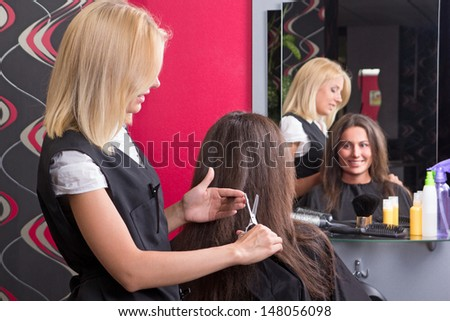 female hairdresser makes hairstyle for beautiful girl in beauty salon - stock photo