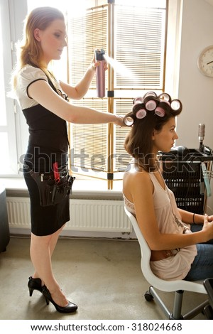 Female hairdresser spraying hairspray in customer's hair - stock photo