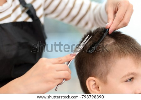 Female hairdresser working with little boy in salon, closeup