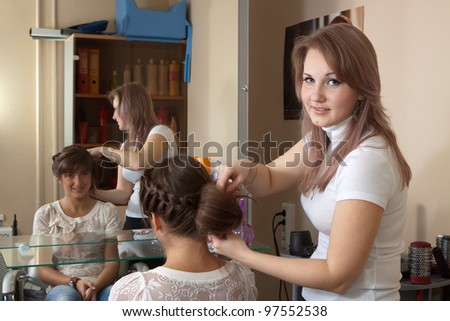 Female hairdresser works on woman hair in salon - stock photo
