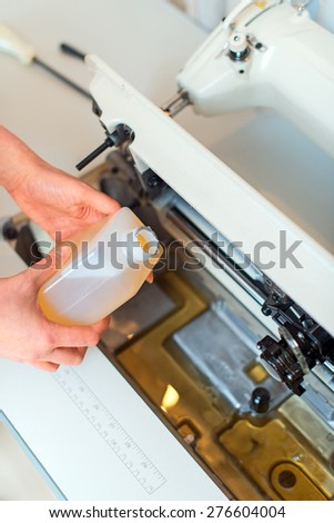 Female hand adding oil in sewing machine. Maintenance. - stock photo