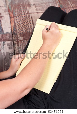 Female Hand and Pen on Writing Tablet - stock photo