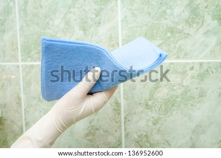 female hand cleaning kitchen tiles with sponge - stock photo