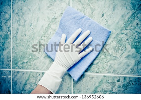 female hand cleaning kitchen tiles with sponge color processed