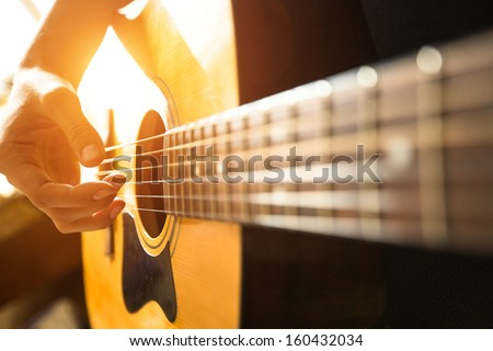 Female hand close-up playing on acoustic guitar. - stock photo