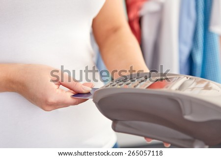Female hand controls payment terminal in shop - stock photo