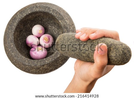 Female hand crushing onions using stone pestle and mortar - stock photo
