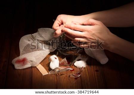 Female hand cut by broken glass in a dark wood. - stock photo