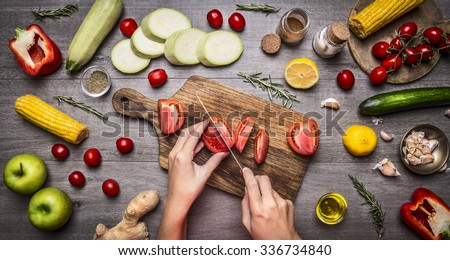 Female hand cut tomatoes on rustic kitchen table, around lie ingredients, vegetables, fruits, and spices, Healthy foods, cooking and vegetarian concept. - stock photo