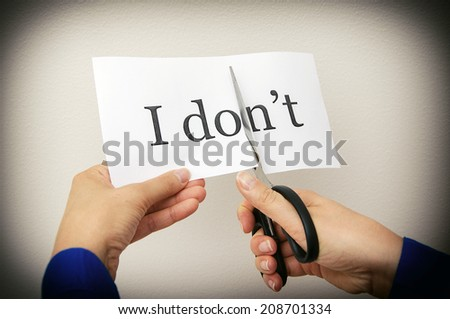 Female hand cutting paper with words. Concept. - stock photo