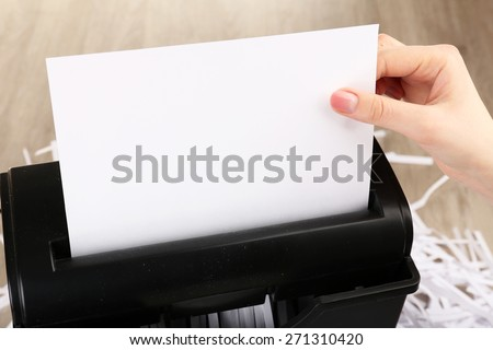 Female hand destroying sheet of paper with shredder on wooden table, closeup - stock photo