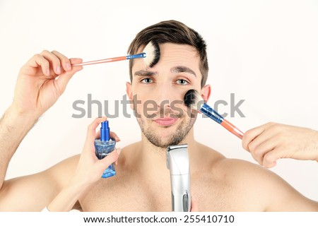 Female hand doing make up young man isolated on white - stock photo