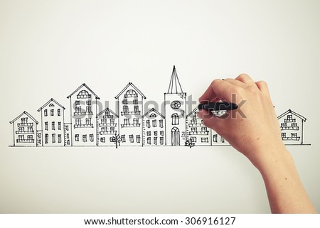 female hand drawing houses on a paper