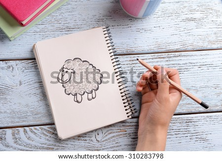 Female hand drawing sheep in notebook on wooden table background - stock photo