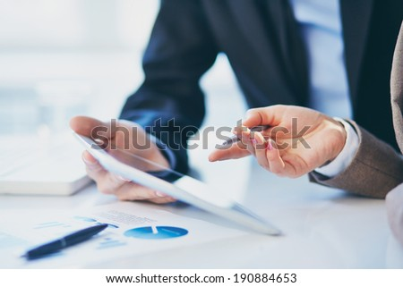 Female hand during explanation of report in touchpad