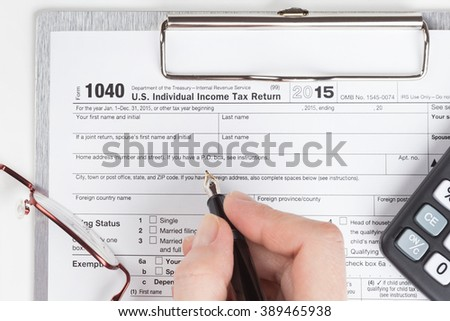 female hand filling out Income Tax Return Form