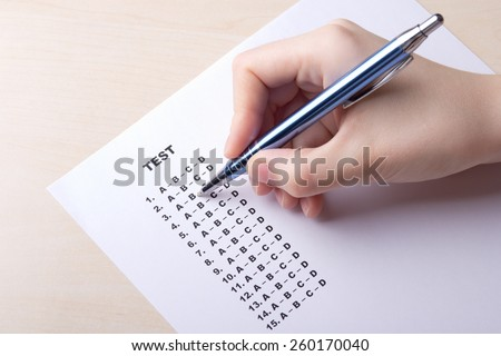 female hand filling test score sheet with answers - stock photo