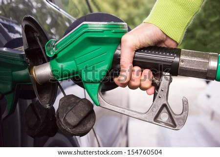 Female hand filling the car tank with gasoline - stock photo
