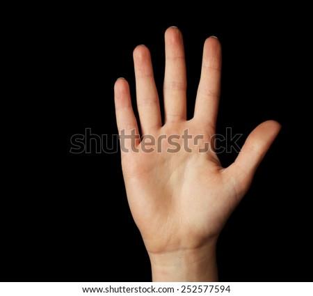 Female hand gesture on black background - stock photo