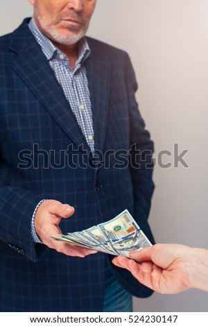 Female hand gives dollar bills to senior man. Money transaction
