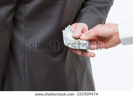 Female hand giving a bribe to businessman - closeup shot - stock photo
