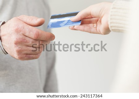 Female hand giving a plastic card to senior male hand - stock photo