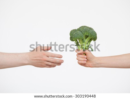 Female hand giving fresh broccoli to somebody, white background