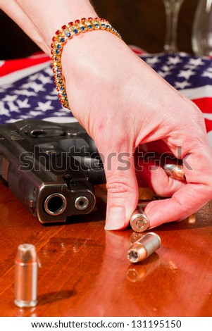 female hand grabbing a hallow point bullet with a gun and an american flag in the background - stock photo