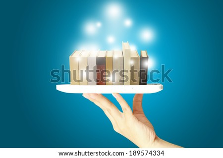 Female hand hold digital tablet with stack of book in E-book concept - stock photo