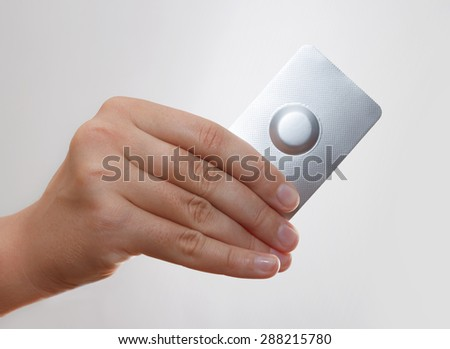 Female hand hold one medical pill in blister pack against grey background - stock photo
