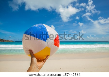 female hand holding a ball at a beautiful beach with a turquoise sea and blue sky, Seychelles - stock photo