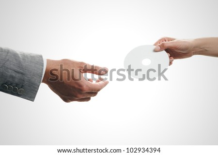 Female hand holding a blank disc, white background - stock photo