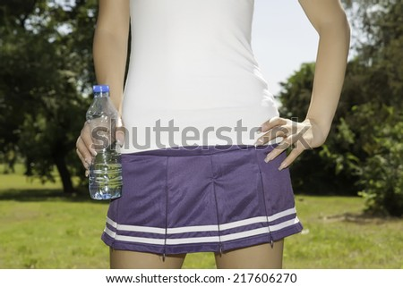 female hand holding a bottle of water - stock photo