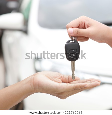 Female hand holding a car key and handing it over to another person isolated