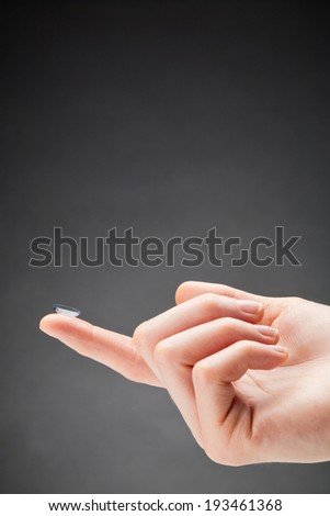 Female hand holding a contact lens on the fingertip of the index finger with copy space above it.