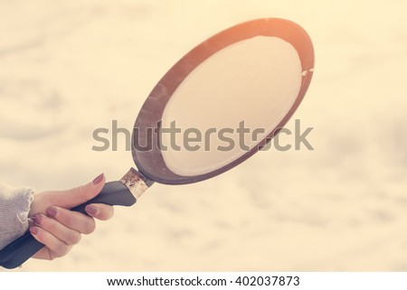 Female hand holding a frying pan with the dough for pancakes in snow