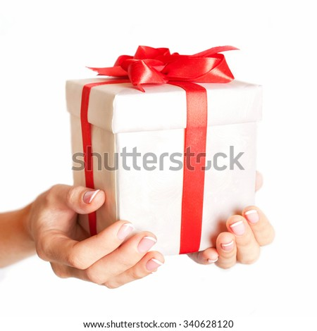 Female hand holding a gift box with a red bow. Time gifts. Christmas, x-mas, happiness concept. Selective focus on the present. Isolated on white background - stock photo