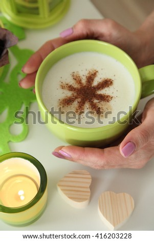 Female hand holding a mug of coffee. Green coffee mug. Cappuccino with cinnamon. Candle in green candlestick. Fresh bakery. Muffins. Hearts made of wood. - stock photo