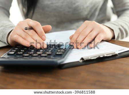 Female hand holding a pen and using calculator while filling in the individual income tax return, close up - stock photo