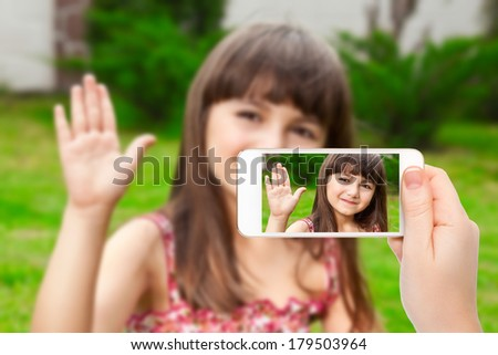 female hand holding a phone with video call of little girl on the screen on a background of green grass