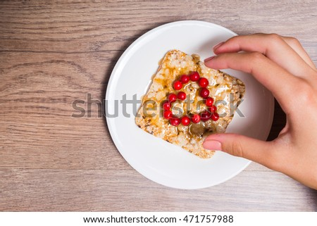 Female hand holding a sandwich of crispy bread, honey and cranberries.